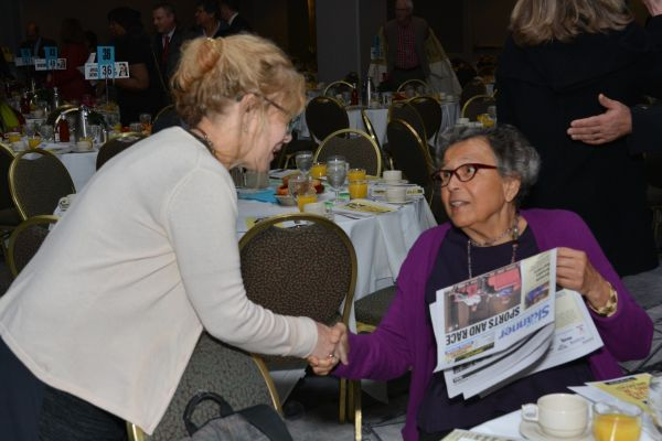 The Skanner's Helen Silvis shakes hands with a guest at the 31st MLK Breakfast, Portland, Jan. 16, 2017 (Mike Norris)