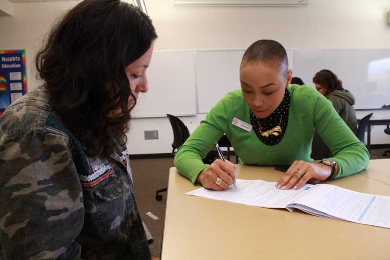 worker helps student apply for Cover Oregon