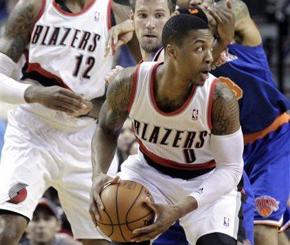 Damon Lillard holds ball as he tries to get past NY Knicks defenders