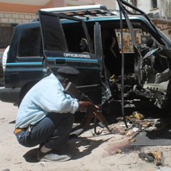 Policeman examines car after bomb