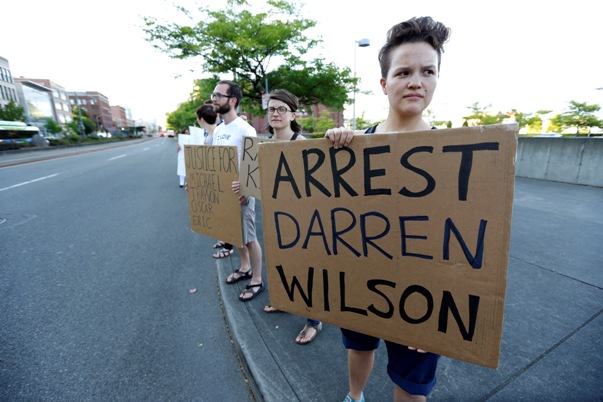 Protester with sign demanding Darren Wilson's arrest