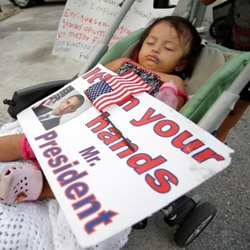 refugee child holding a sign for President Obama