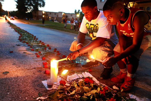 Theo Murphy and his brother Jordan Marshall light candles at a memorial on Canfield Drive in Ferguson