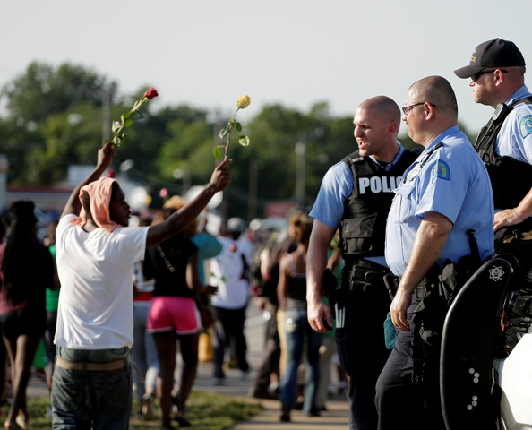 Police watch as protesters march in Ferguson