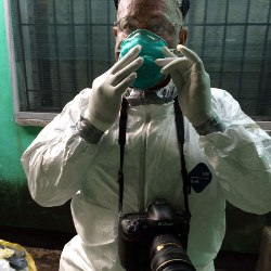 MIchel du Cille in protective clothing before photographing ebola patients
