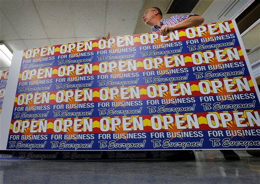"Scott Koehler, the sales director at Fast Signs, takes a sheet of anti-Senate Bill 1062 signs that read ""Open For Business To Everyone"" off the printer, Wednesday, Feb. 26, 2014 in Phoenix. Arizona"