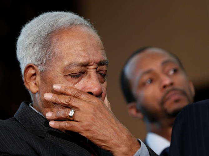Albert Brinson cries as Bernice King speaks during a news conference