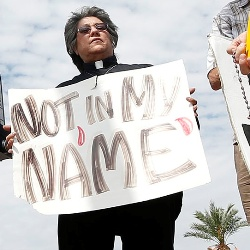 "Protester with sign saying ""Not in My Name"""
