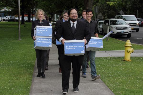 Pot legalization advocates carry boxes of petitions