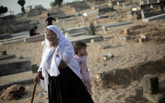Palestinian woman visits the graves of relatives