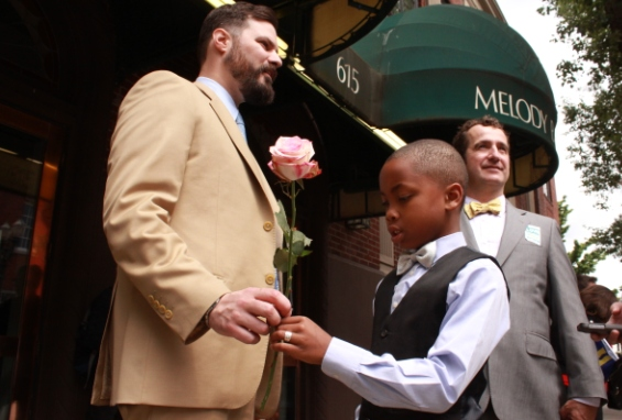 Boy gives rose to his father as they celebrate the passing of same-sex marriage in oregon