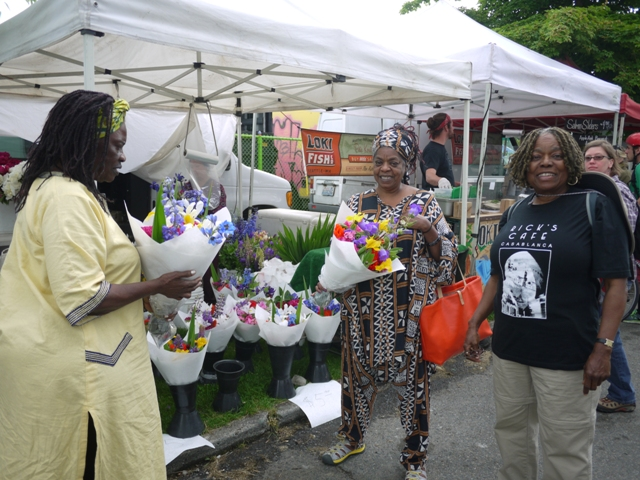 Dawn Mason buys flowers at the Columbia City Farmers Market
