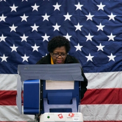 Woman voting in front of flag