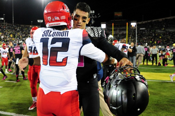 Arizona player hugs Oregon Quarterback Marcus Mariota