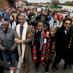 Protesters, including Dr. Cornel West, march arm in arm