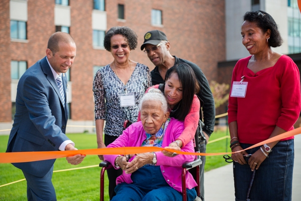 Genevieve Tebeau cuts the ribbon to the new residence named after her late husband