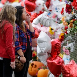 Students look at the fence of remembrances for victims of Marysville School shooting