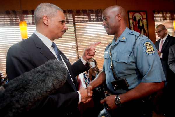 Eric Holder shakes hands with Capt. Ron Johnson of the Missouri State Highway Patrol at Drake's Place Restaurant in Florrissant, Mo.