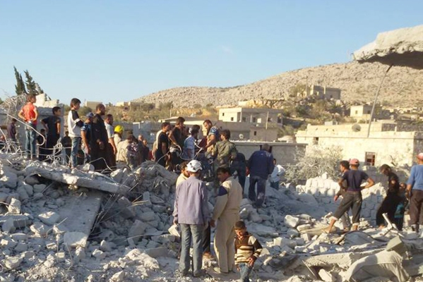 Syrian villagers examine house destroyed by US/Arab coalition airstrikes in Kfar Derian