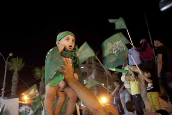 Palestinians raise a baby girl clad in green flags in the air at a protest