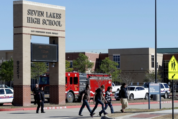 students pass by Seven Lakes High School