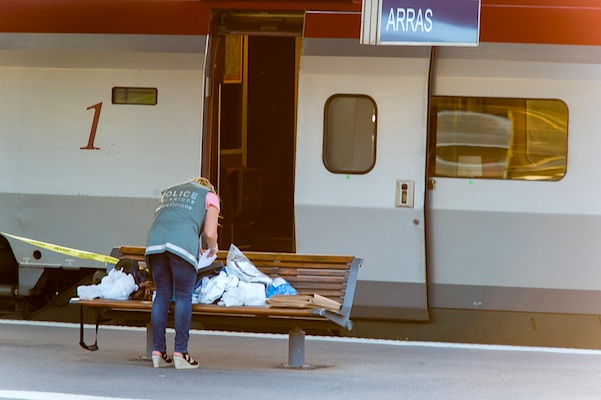French police officer gathers evidence on train platform