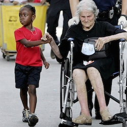 "In this Sept. 3, 2005 file photo, Tanisha Blevin, 5, holds the hand of fellow Hurricane Katrina victim Nita LaGarde, 105, as they are evacuated from the convention center in New Orleans. Photographer Eric Gay recalled, ""It was a sweet moment. Kind of uplifting despite the whole ordeal."" (AP Photo/Eric Gay, File)"