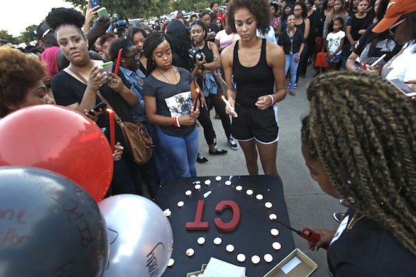 Friends and family gather to put together a tribute at a candlelight vigil for Christian Taylor, held in the parking lot of Koinonia Christian Church in Arlington, Texas, Saturday, Aug. 8, 2015. The FBI has been asked to help investigate the death of Taylor, a Texas college football player, who was fatally shot by an officer during a burglary call at a car dealership, a suburban Dallas police chief said Saturday. (Louis DeLuca/The Dallas Morning News via AP)