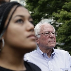 Marissa Johnson, left, speaks as Mara Jacqueline Willaford stands with her and Democratic presidential candidate Sen. Bernie Sanders, I-Vt., stands nearby as the two women take over the microphone at a rally Saturday, Aug. 8, 2015, in downtown Seattle. The women, co-founders of the Seattle chapter of Black Lives Matter, took over the microphone moments after Sanders began speaking and refused to relinquish it. Sanders eventually left the stage without speaking further and instead waded into the crowd to greet supporters. (AP Photo/Elaine Thompson)