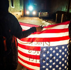 "Demonstrator holding an American flag with the words ""Black Lives Matter"" written on it"