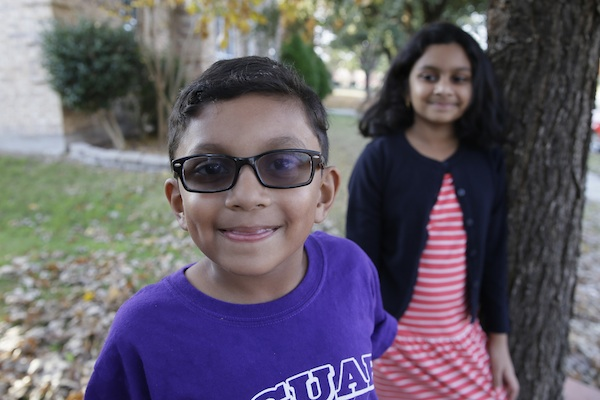 Yaseem Shakil, 7, smiles for a photo with his sister Noreen Shakil, 9, outsider their home in McKinney, Texas, Friday, Dec. 11, 2015. Donald Trumps' remarks in the wake of the Dec. 2 shooting attack in San Bernardino, Calif., have stoked fears in Muslim children across the U.S. Their young minds, parents say, are confused about who the screaming man on TV is, what he's saying about their faith and why thousands of their fellow Americans are cheering him on.(AP Photo/LM Otero)