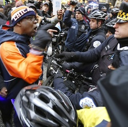 A protesters yells at a Chicago Police officer at a bicycle barricade on Chicago's Magnificent Mile Thursday, Dec. 24, 2015, in Chicago. The Christmas Eve Day protest calling for the resignation of Mayor Rahm Emanuel is the latest in a series of demonstrations in the city since the release last month of police video showing a white officer shoot a black teenager 16 times. (AP Photo/Charles Rex Arbogast)
