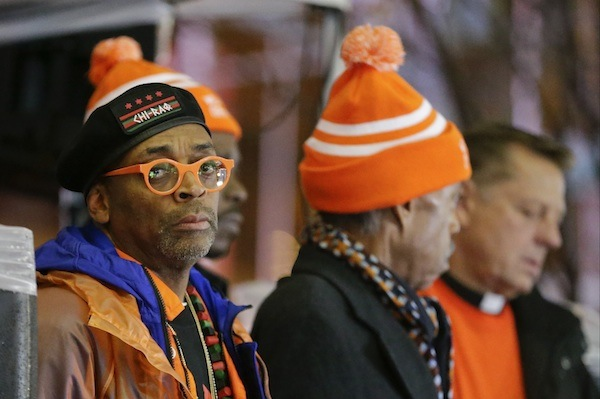 "Spike Lee, left, listens to speakers during a rally for the prevention of gun violence Tuesday, Dec. 1, 2015, in New York, following the premiere of his new film ""Chi-Raq."" (AP Photo/Frank Franklin II)"