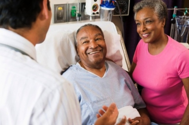 African American man, wife speaking to doctor