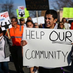 demonstrators in Pasco hold sign that reads 'Help Our Community'