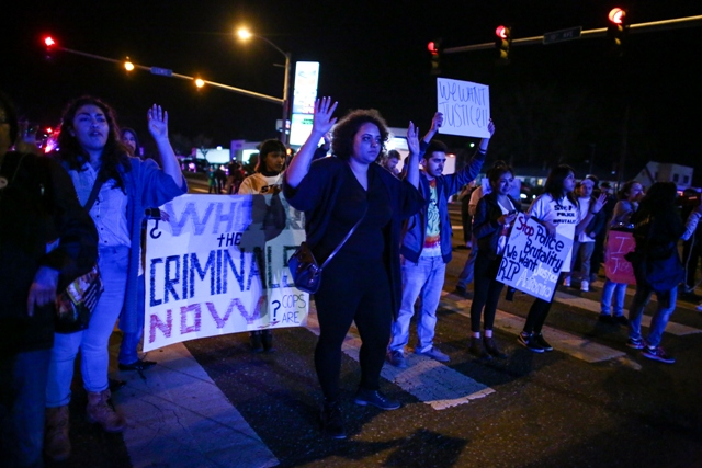 demonstrators in Pasco march with hands in 'don't shoot' pose