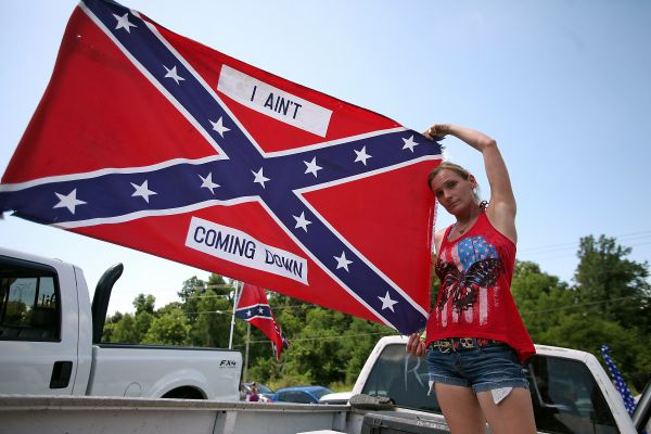 Vicksburg resident Nancy Pettway holds up a flag before a Confederate flag rally in Vicksburg, Miss., Saturday, July 18, 2015. (Justin Sellers/The Vicksburg Evening Post via AP)