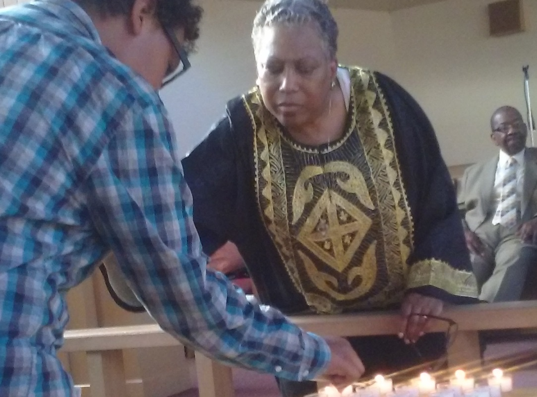 Rev. Terry McCray Hill, pastor of Bethel AME Church in Portland, helps a community member light a candle at a vigil for victims of last's week's shooting in Charleston, S.C.