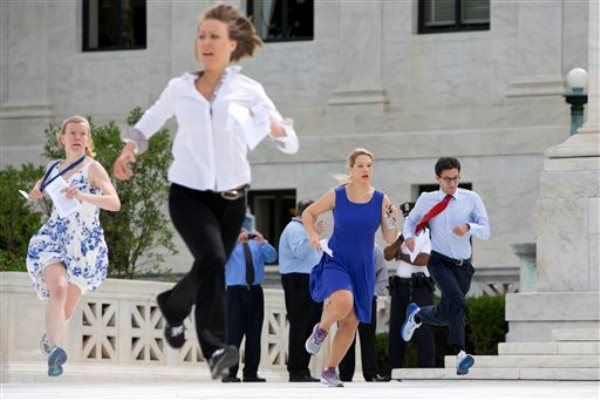 Interns run across the plaza of the Supreme Court in Washington