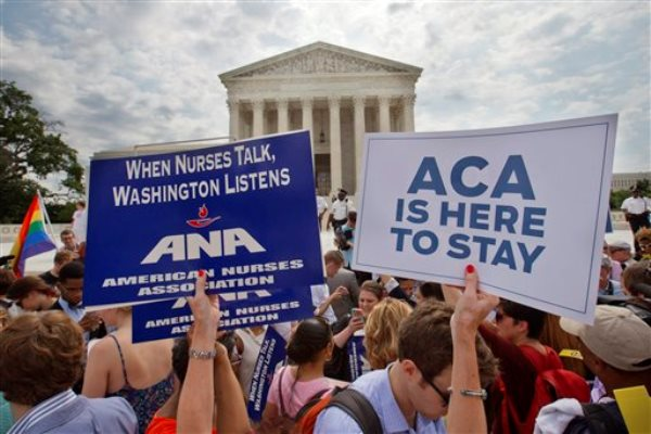 Supporters of the Affordable Care Act hold up signs as the opinion for health care is reported outside of the Supreme Court in Washington.