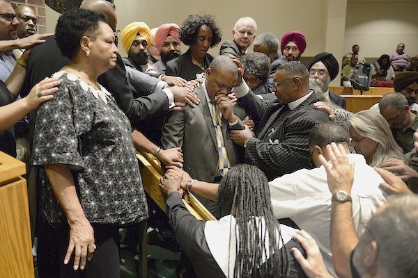 Religious leaders surround Rev. Dr. Timothy Tyler, at center with hand to face, Pastor at the Shorter Community African Methodist Episcopal Church