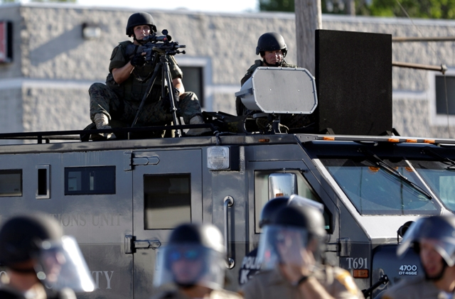 a police tactical team points rifles at the crowd in Ferguson, Missouri