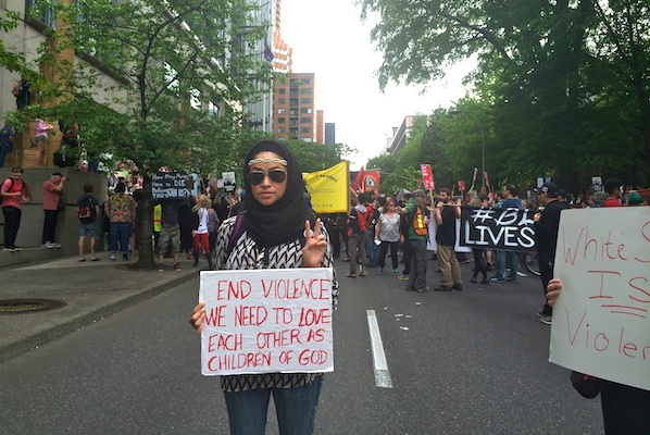 Portland MayDay protester holding end violence sign