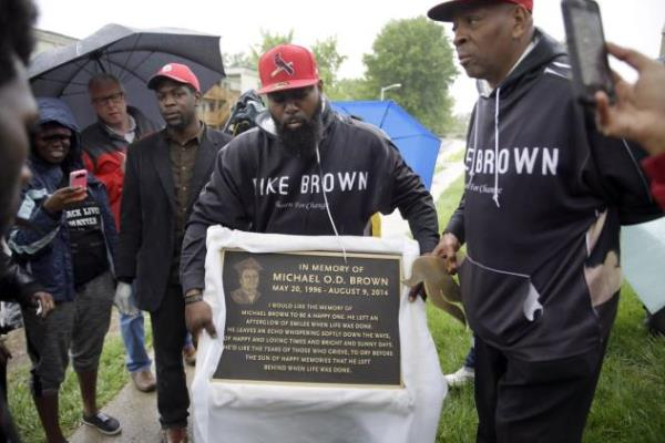 Mike Brown Sr. holds a placque of his late son Mike Brown Jr.