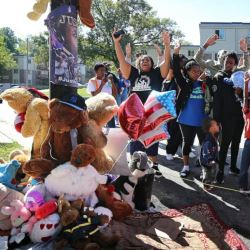 Protesters stand with their hands up at a makeshift memorial for Mike Brown near where the late teen was shot and killed by Ferguson police officer, Darren Wilson