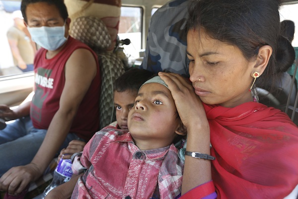 A Nepalese mother takes her injured son to a hospital in an ambulance in Chautara, Sindhupalchok district, Nepal