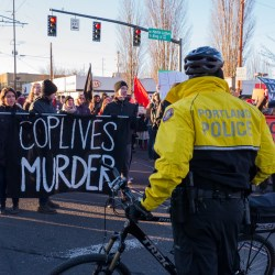 Demonstrators march along Northeast Martin Luther King boulevard on Black Friday while police look on
