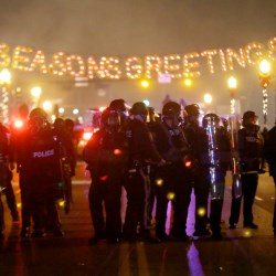 Police gather on the street as protesters react after the announcement of the grand jury decision in Ferguson, Missouri
