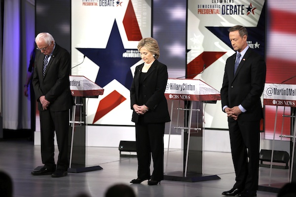 Democratic presidential candidates Bernie Sanders, left, Hillary Rodham Clinton and Martin O'Malley take takes a moment of silence for those killed in the Paris attacks before a Democratic presidential primary debate, Saturday, Nov. 14, 2015, in Des Moines, Iowa. (AP Photo/Charlie Neibergall)