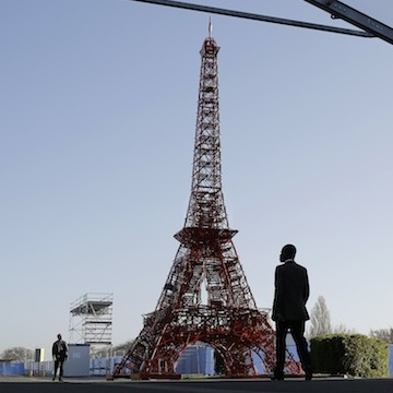 People walk in front of a reproduction of the Eiffel tower at the United Nations Climate Change Conference in Le Bourget, outside Paris, Saturday, Nov. 28, 2015. The site of Paris-Le Bourget will officially become United Nations territory for the COP 21 conference which is scheduled to start on Nov. 30. (AP Photo/Laurent Cipriani)